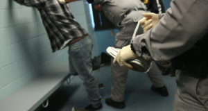 CAMARILLO, CA - OCTOBER 14:  A U.S. Immigration and Customs Enforcement (ICE), contractor removes the shoelaces from a detained immigrant at a processing center on October 14, 2015 in Camarillo, California. ICE builds deportation cases against thousands of both undocumented and Green Card holding immigrants convicted of crimes. The number of ICE detentions and deportations from California has dropped since the state passed the Trust Act in October 2013, which set limits on California state law enforcement cooperation with federal immigration authorities.  (Photo by John Moore/Getty Images)